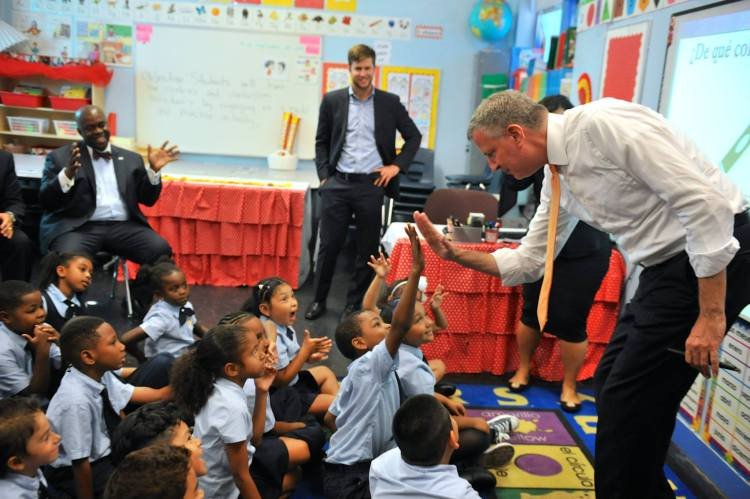 New York Mayer Bill de Blasio high-fiving schoolchildren in the Amber Charter School, Manhattan.