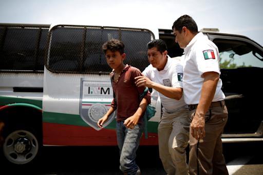 Dos empleados de Migraciones que detienen a un chico de Centroamérica