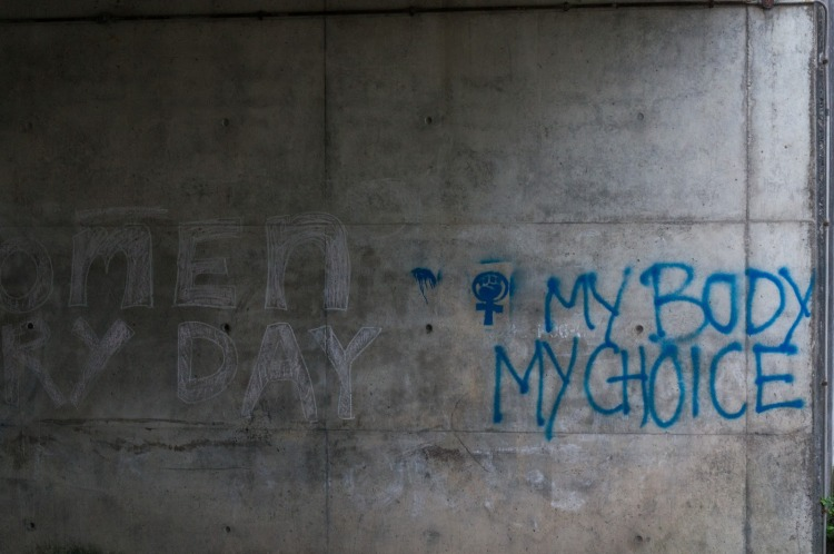 """Graffiti under a bridge saying """"MY BODY / MY CHOICE"""" in blue letters, preceded by the feminist symbol of a clenched fist within the Venus symbol."""