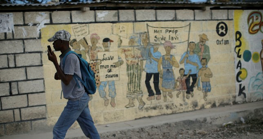 A man walking past an Oxfam sign a camp set up by the charity in Haiti.